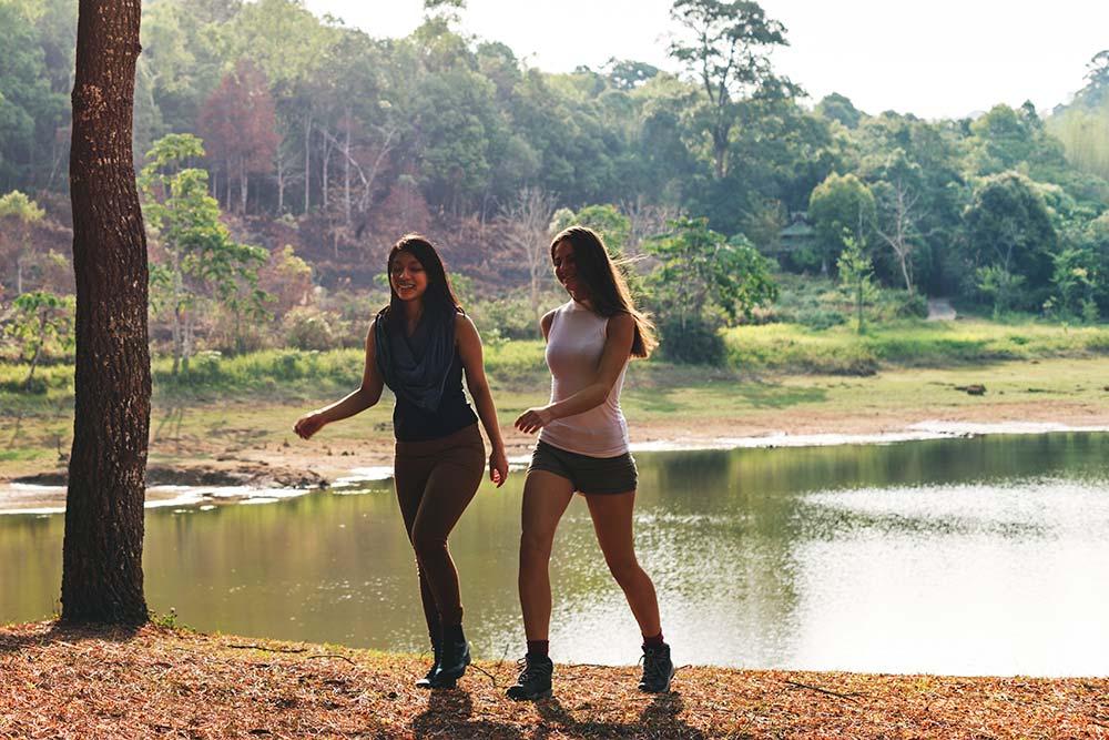 two girls  walking in woods